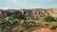 Car Driving Through The Nature Scenery On Road Trip In America In The Afternoon With Sunlight Shining On Hills. Amazing Nature Power Build The Beautiful High Desert Mountains With Blue Sunshine Sky