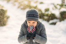 A Boy Warms His Hands From The...