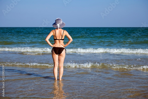 1a7c1a29c22eb Young girl in a bathing suit and a striped hat is standing in the sea with