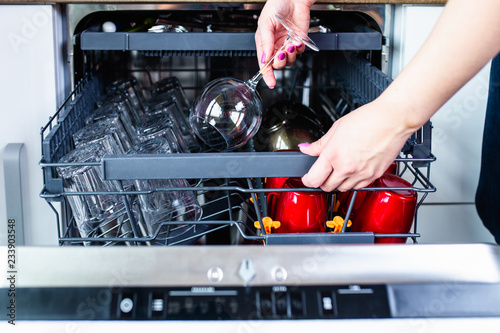 Woman's hand with an open dishwasher filled with clean dishes.