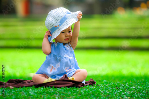 isolated candid portrait of sweet and adorable Asian Korean baby girl 3 or 4  months old playing with hat alone at city park sitting on green grass in ... f787cdbc334