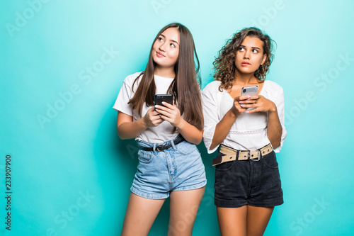Fotografia  Photo of curious african american woman peeking at mobile phone of asian girl in