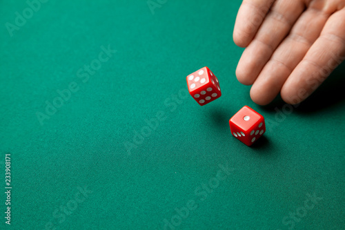 Photo  Man holds two red dices and throws them on green poker gaming table in casino