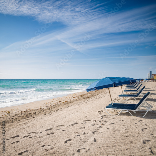 Keuken foto achterwand Verenigde Staten Open umbrellas on the sandy shore near the ocean. Beach in Miami, Florida. Empty beach. Seaside. Early morning. Clouds