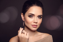 Beauty Makeup Portrait. Fashion Model Golden Jewelry. Beautiful Young Woman With Make-up, Expensive Earrings And Rings. Elegant Lady Isolated On Dark Background Showing Luxurious Jewellery Set.