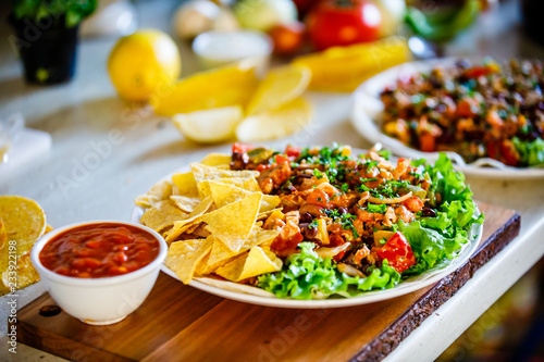 Grilled meat with nachos and vegetables on wooden background