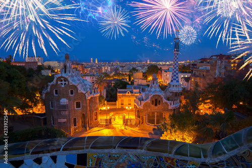 Gaudi bench and cityscape of Barcelona from park Guell at night with fireworks, Spain