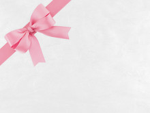 Pastel Pink Ribbon Bow Wrapped Around Corner Of White Paper With Abstract Striped Pattern, Double Tied Bow And White Cardboard For Cover Gift Box Decor Or Greeting Card, Flat Lay Close Up Top View