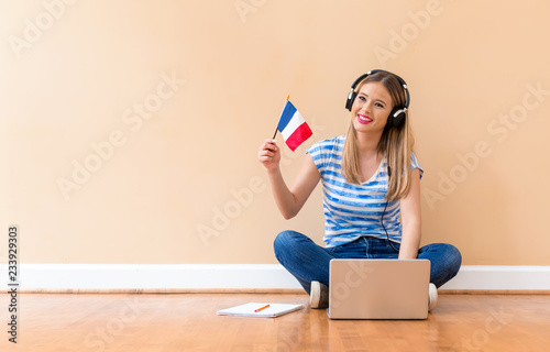Obraz Young woman with French flag using a laptop computer against a big interior wall - fototapety do salonu