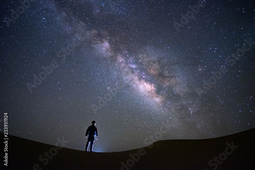 Photo Milky way galaxy with a man standing and watching at Tar desert, Jaisalmer, India