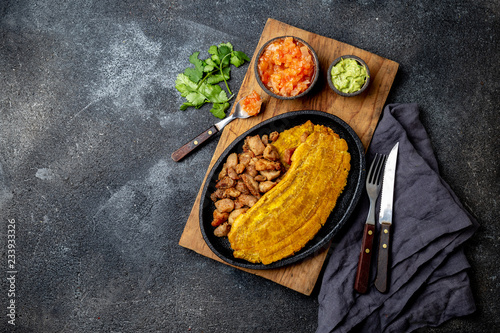 Photo Stands Ready meals COLOMBIAN CARIBBEAN CENTRAL AMERICAN FOOD. Patacon or toston, fried and flattened whole green plantain banana on white plate with tomato sauce and chicharron Black background, top view