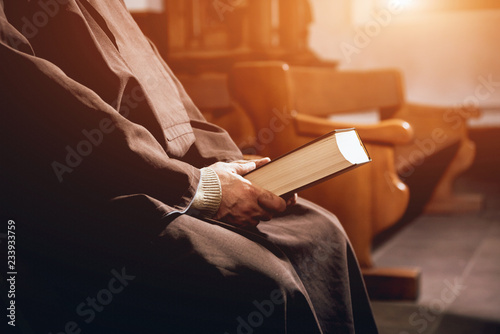 A monk in robes with holy bible in their hands praying in the church Canvas Print