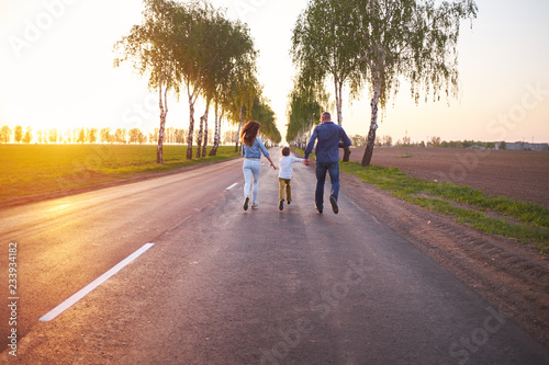 Fototapeta  Happy family dad mom and son, playing, run away in the fresh air on the road nea