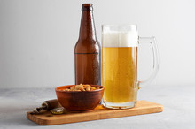 Lager Beer Pouring In Glass And Bottle With Salted Peanuts On Gray Concrete Background