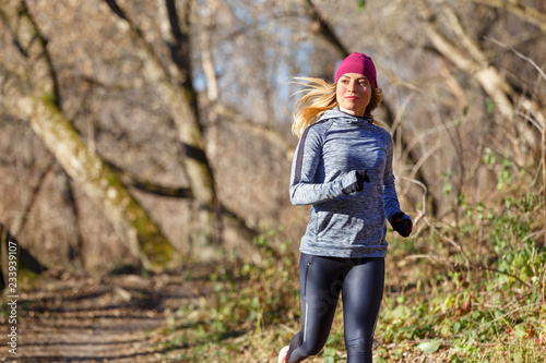 Staande foto Jogging Young woman jogging on trail in autumn park