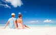back view of couple in bright clothes and hats sitting at tropical beach