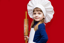 Happy Little Girl In Chef Uniform Holds Rolling Pin Isolated On Red. Kid Chef. Cooking Process Concept