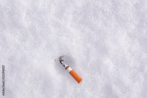 Fényképezés  top view of smoking cigarette butt on a snow with copy space