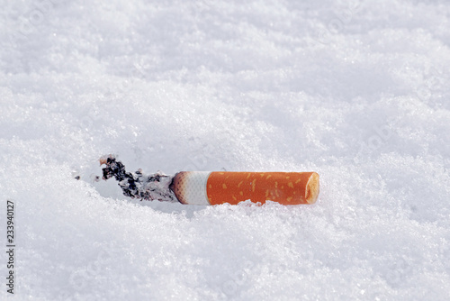 Fotografija  closeup of smoking cigarette butt on a snow with copy space