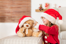 Cute Young Girl Wearing Santa Hat Playing With Her Christmas Present, Soft Toy Teddy Bear. Playful Kid At Christmas Time With Soft Toy.