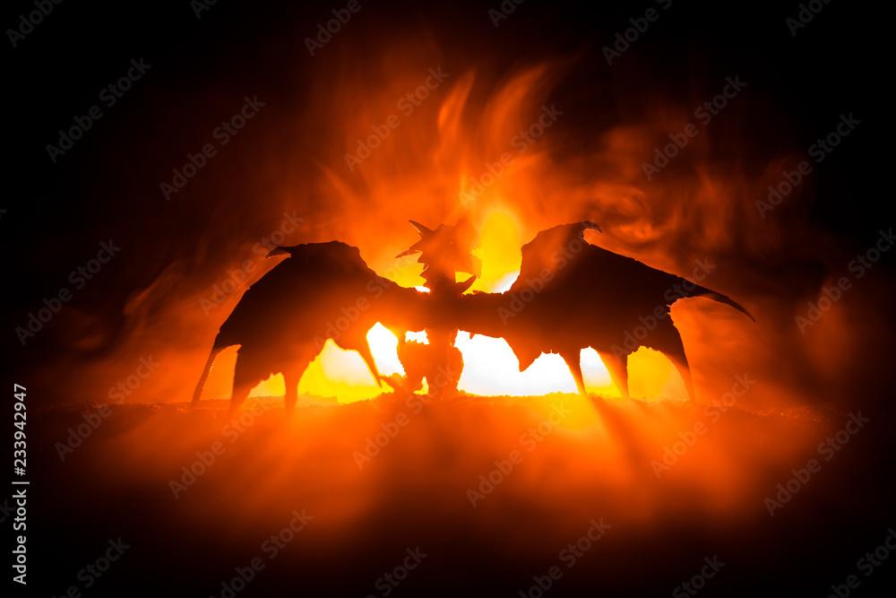 Fototapeta Silhouette of fire breathing dragon with big wings on a dark orange background