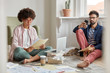 Photo of young stratuppers collaborate together, work at home, sit on floor in living room, think about business investment. Black curly woman in spectacles holds documents, unshaven guy chats online