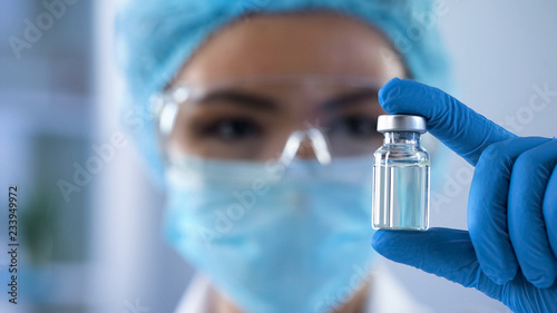 Fotografia  Lady scientist looking at ampoule with new medication, vaccination development