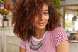 Headshot of attractive woman with curly hair, looks positively at camera, satisfied with something, wears striped t shirt and silver jewellery, models in restaurant. Close up of dark skinned girl