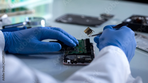 Fotografie, Obraz  Technician holding computer part with lancet, computer safety, it industry