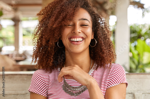 Obraz Headshot of glad woman laughs and smiles broadly, expresses positive emotions, has hilarious expression, wears round big earrings and necklace, spends time in cafe. Afro American teenager indoor - fototapety do salonu