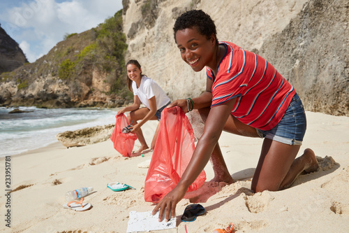 Fotografía Photo of active responsible volunteers gather litter on sandy beach, fight against contamination, pose on coastline where is too much garbage, pose against cliff background