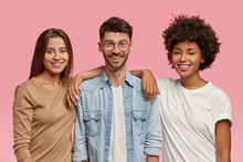 Horizontal Shot Of Three Mixed Race Teenagers Spend Time Together, Pose For Common Photo Against Pink Background. Satisfied Guy In Eyewear And Denim Shirt Stands Between Two Cheerful Women Indoor