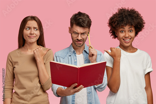 Foto  Indoor shot of Caucasian and African women point at their nerd friend who looks in book with puzzlement, learns information, being busy with studying, isolated over pink background