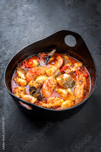 Traditional French Corsican seafood stew with prawns, mussels and fish as top view in a modern design Japanese cast-iron roasting dish