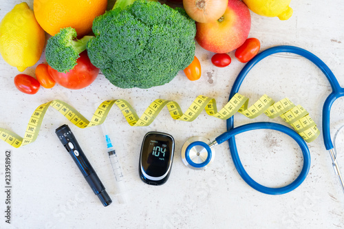 raw vegetables with blood glucose meter, syringe, lancet and stethoscope on desk, diabetes healthy diet concept
