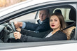 Beautiful woman with instructor sitting in car