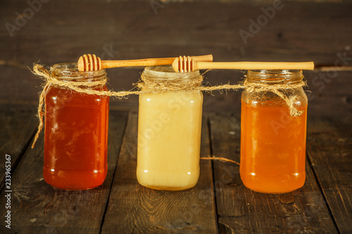 Poster Sap Different types of honey in glass jar on wooden rustic background. Honey in a glass jar. Honey is a healthy diet.