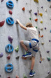 Activity of rock-climbing on artificial climbing wall, Caucasian boy with safety line