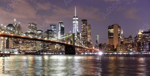 Fototapeta New York City, financial district in lower Manhattan with Brooklin Bridge at night, USA obraz na płótnie