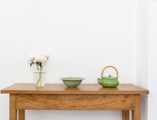 Pale Pink Peonies In Glass Vase With Green Bowl And Teapot On Wooden Sidetable Against White Wall (selective Focus)