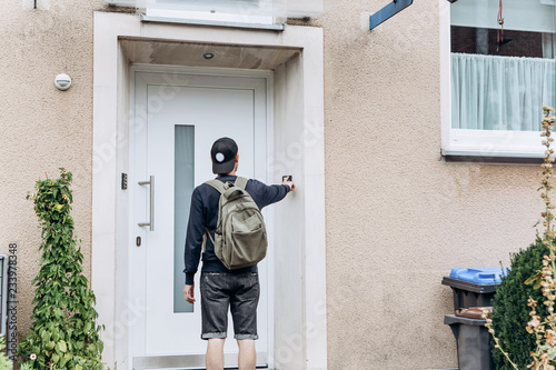 Vászonkép  The tourist rings the doorbell to check in to the room he has booked or the student with the backpack returns home after classes at the institute or on vacation