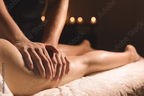 obraz PCV A masseur in a dark room does a hip massage with oil for a woman. Spa procedures massage women