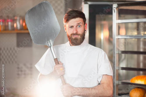Fotografía  A young funny baker with a pizza spatula in his hands against the backdrop of an