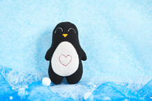 One Handmade Soft Toy Penguin On A Blue Background