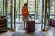 Woman carrying suitcase bag from hotel for travelling.