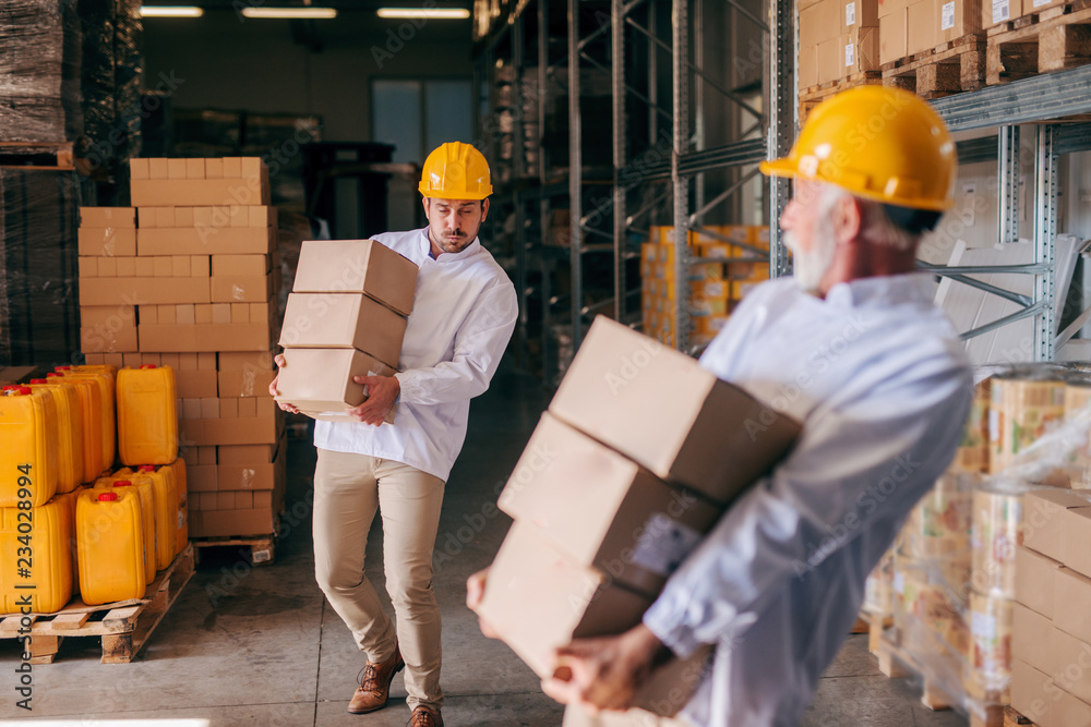 Fototapety, obrazy: Coworkers carrying boxes with helmets on heads. Storage interior.