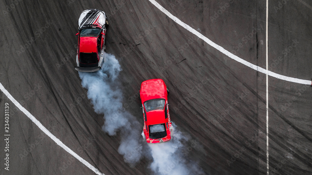 Aerial view two cars drift battle view from above, Activity two cars drift action battle on asphalt race track with abstract smoke.
