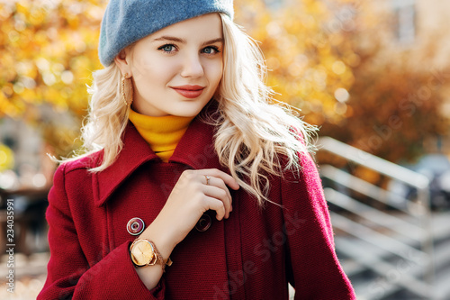 Happy smiling girl wearing burgundy, marsala coat, blue beret, yellow turtleneck, golden wrist watch, hoop earrings posing in street. Autumn fashion, advertising concept. Copy, empty space for text