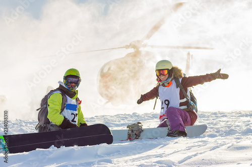 Door stickers Winter sports pair of freeriders of snowboarders on background helicopter lands