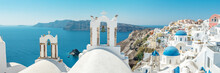 Panoramic View Of Oia Town With Traditional And Famous Houses And Churches With Blue Domes Over The Caldera On Santorini Island. Greece.